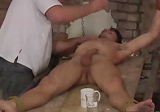 Restrained twink receives a blowjob and candle torment from dom